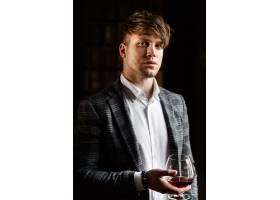 穿着灰色西装的英俊青年端着一杯威士忌站着_1621115