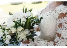 令人惊叹的黑发新娘手持丰富的白色婚礼花束_1620835