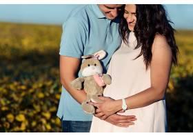 玩具兔躺在年轻准夫妇的怀里_1620665