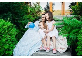 穿着蓝色连衣裙的女孩和妈妈在玩小蓝球_1617258