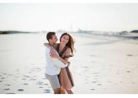 穿着鲜艳刺绣衣服的赤脚情侣在白色的沙滩上_1621663