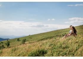 男人和女人在美丽的风景前拥抱坐在草地上_1621696