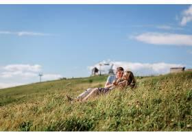 男人和女人在美丽的风景前拥抱坐在草地上_1621697