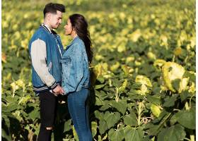 美丽的年轻情侣站在向日葵的田野上_1623489