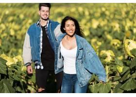 美丽的年轻情侣站在向日葵的田野上_1623490
