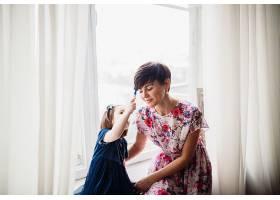 母亲带着女儿坐在窗台上_1617226