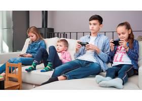 孩子们拿着控制器在青少年附近浏览智能手机_2041319