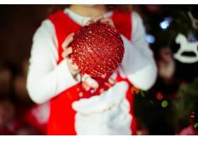 小女孩怀里抱着红色圣诞树玩具_1617067