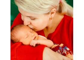一名妇女在怀里亲吻娇嫩的新生儿_1617098