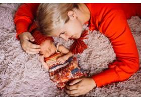 一名妇女拥抱躺在粉色毯子上的新生儿_1617074