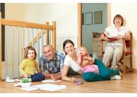 一对微笑的夫妇带着他们的孩子和祖母在客厅_1631091