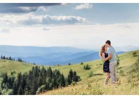 一对情侣站在青山上温柔地拥抱着绚丽的风景_1621694