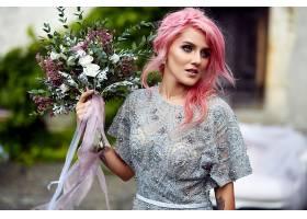 令人惊叹的粉色头发女人站在那里手持大束_1621124