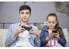 微笑的兄弟姐妹手持智能手机和控制器_2041345