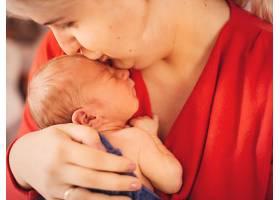 身穿红色连衣裙的母亲胸前抱着梦幻般的孩子_1617078