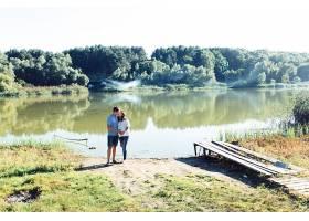 迷人的期待情侣站在绿色的河边拥抱着_1620655