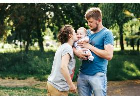 年轻的家庭母亲父亲和小儿子在公园里开_1620607