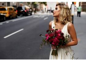 手持红色花束的令人惊叹的新娘站在纽约街头_1621233