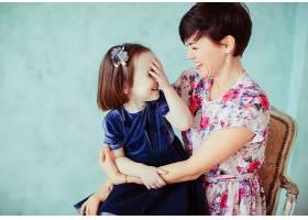 抱着女儿的母亲坐在椅子上_1617232
