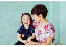 抱着女儿的母亲坐在椅子上_1617233