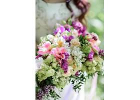 新娘手持由白色和紫罗兰色花朵制成的丰富的_1621013