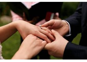 新郎把结婚戒指戴在新娘的手指上_1621248
