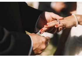 新郎把结婚戒指戴在新娘的手指上温柔地握_1621707