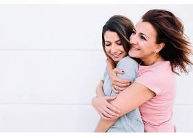 欢快的女人在白墙附近拥抱女人_2111141