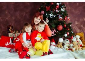 母亲和她的孩子们坐在圣诞树前_1617059