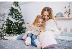 母亲和美丽的金发女婴打开礼物_1533622