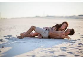 女人拥抱躺在白色沙子上的蛇男人_1621666