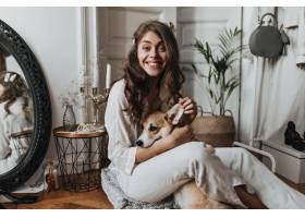 白色衬衣的卷曲妇女获得与狗的乐趣_15970915