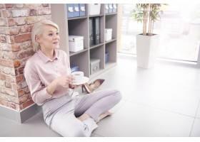 妇女坐与咖啡的地板在办公室_15971142