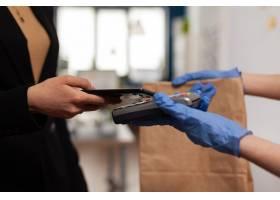 送货人佩带的保护手套接受从使用智能手机nf_15853540