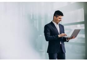 有膝上型计算机的年轻英俊的商人在办公室_7435586