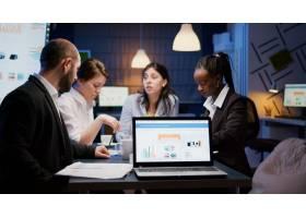 有财政图表的便携式计算机在站立在会议桌上_15854118