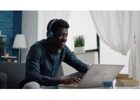 年轻人佩带的耳机键入在膝上型计算机使_15854085