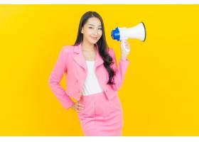 与扩音机的画象美丽的年轻亚裔妇女微笑在黄_14889046