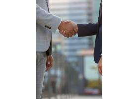 站立在城市街道和握手的买卖人_5889276