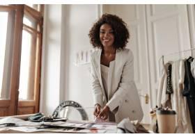 快乐兴奋的卷曲黑皮女人在超大的白色夹克真_15971170