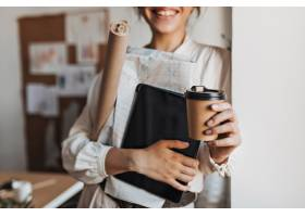 酷女人拿着文件和咖啡杯_15970835