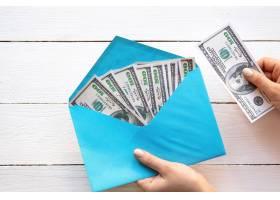 拿着与金钱木背景的女性手一个信封财务_14203102