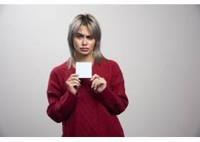 拿着在灰色背景的哀伤的妇女拿着备忘录垫_16146407