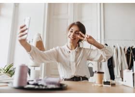 时髦的衬衫的快乐的妇女采取selfie和显示和_15970763