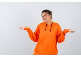 显示在橙色连帽衫的妇女欢迎姿态并且看起来_16147396