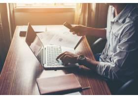 使用手机的商人手有膝上型计算机的在办公桌_1025839