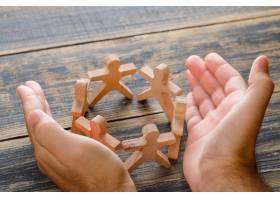 在木桌顶视图的企业成功概念手保护人的木_9426580