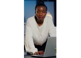 站立在书桌附近的非洲女商人看前面在读邮件_15853532