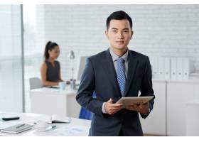 站立在办公室中间和拿着数字式片剂的亚洲商_5839815