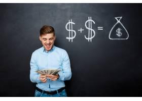 站立在有拉加的美元概念的黑板的英俊的人_7678763